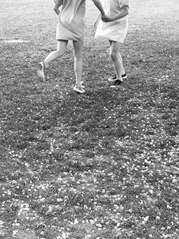 Puistossa juoksentelevat kesämekkoiset tytöt